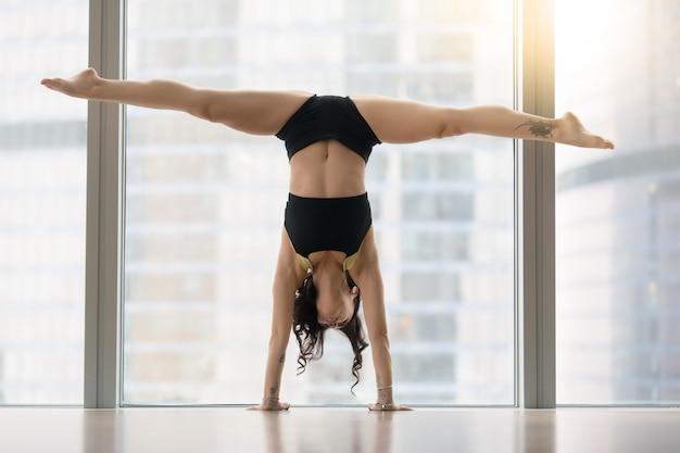 Junge attraktive frau in der tanzhaltung gegen bodenfenster Kostenlose Fotos