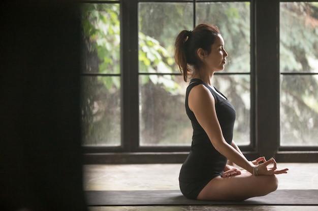 Junge attraktive frau in lotus-haltung, studiohintergrund Kostenlose Fotos