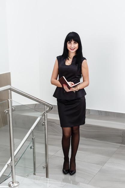 Junge attraktive glückliche brunettefrau kleidete in einem schwarzen anzug an, der mit einem notizbuch arbeitet und stand in einem büro und lächelte. Premium Fotos