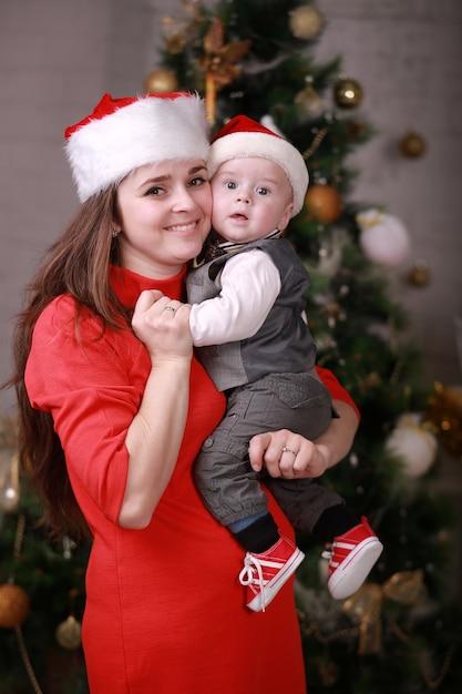 Junge attraktive glückliche mutter in weihnachtsmütze haben eine gute zeit mit ihrem sohn zu hause in der nähe von weihnachtsbaum. familie, glück, feiertage, neujahrskonzept Premium Fotos