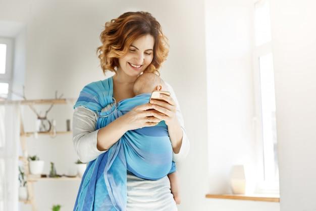 Junge attraktive mutter lächelt und schaut durch fotos des sohnes auf dem handy Kostenlose Fotos