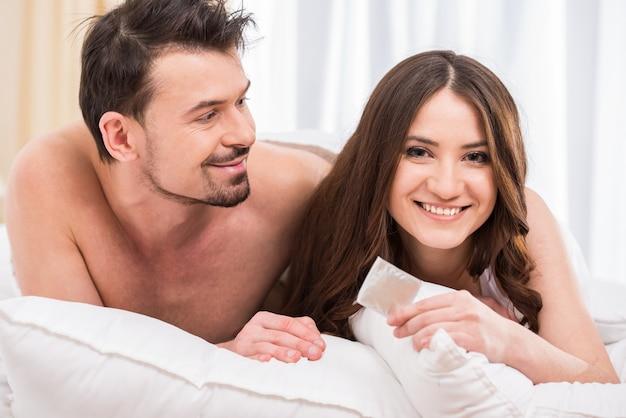 Junge attraktive paare im bett mit einem kondom. Premium Fotos