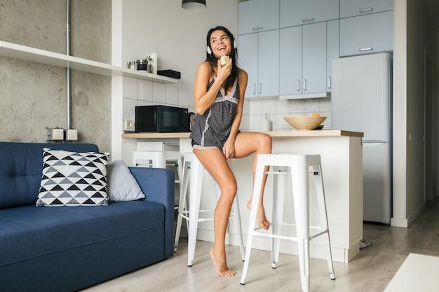 Junge attraktive sexy frau, die frühstück in der stilvollen modernen küche am morgen isst, apfel isst, lächelt, glücklich, positiv, gesunder lebensstil, musik auf kopfhörern hört, lacht, spaß hat Kostenlose Fotos