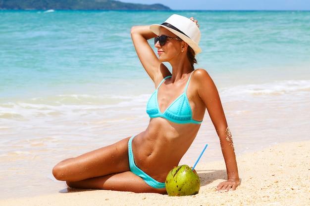 Junge attraktive sexy frau im urlaub, die auf dem sandigen strand durch meer sitzt Premium Fotos