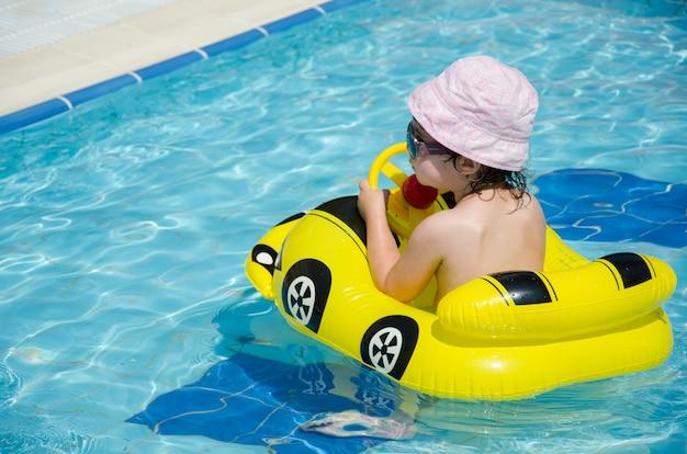Junge auf einem aufblasbaren gelben auto im pool Premium Fotos