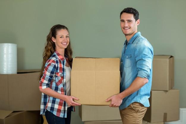 Junge aufwerfende paare beim auspacken von kartonkästen im neuen haus Premium Fotos