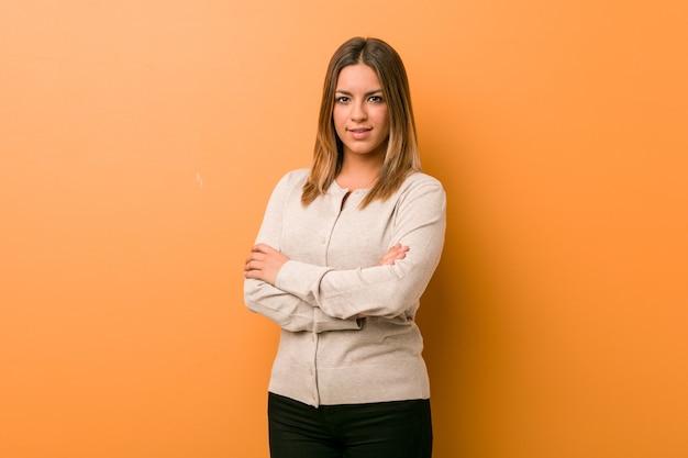 Junge authentische charismatische echte menschenfrau gegen eine wand, die zuversichtlich mit verschränkten armen lächelt. Premium Fotos