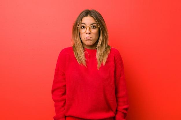 Junge authentische charismatische wirkliche leutefrau gegen eine wand zuckt die verwirrten schultern und offenen augen. Premium Fotos
