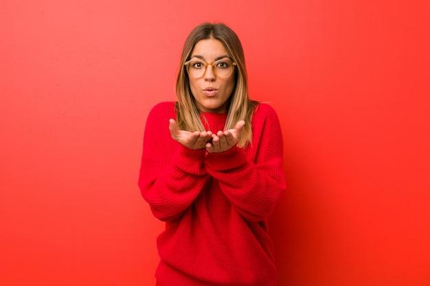 Junge authentische charismatische wirkliche leutefrau gegen faltende lippen einer wand und halten von palmen, um luftkuss zu senden. Premium Fotos