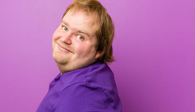 Junge authentische rothaarige dicker mann schaut lächelnd, fröhlich und angenehm zur seite. Premium Fotos