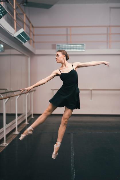 Junge ballerina, die im tanzstudio übt Kostenlose Fotos
