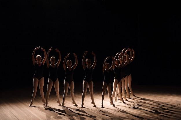 Junge ballerinas, die einen choreografierten tanz üben, regnen während des übens in einer ballettschule alle ihre arme in anmutiger übereinstimmung Premium Fotos