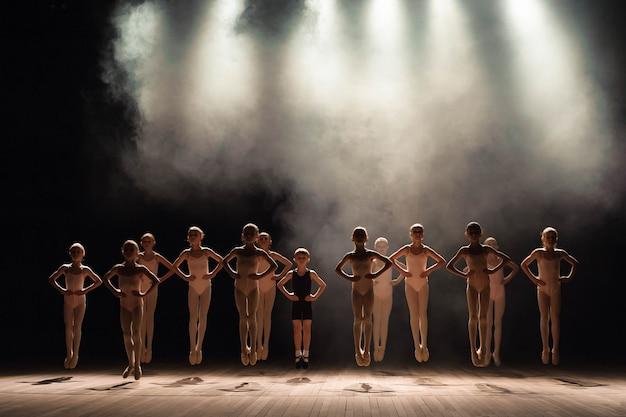 Junge ballerinas proben in der ballettklasse. sie führen verschiedene choreografische übungen durch und stehen in unterschiedlichen positionen. Premium Fotos
