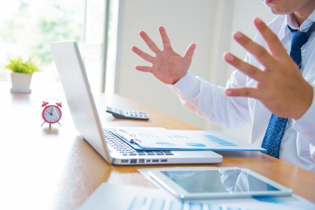 Junge betonte gut aussehend kaufmann am schreibtisch in modernen büro schreien auf laptop-bildschirm und wütend über die finanzielle situation, eifersüchtig auf rivalisierende fähigkeiten, nicht in der lage, client-bedürfnisse zu erfüllen Premium Fotos