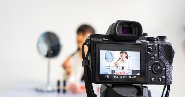 Junge bloggerin, die vlog video auf kamerabildschirm mit make-up-kosmetik zu hause überprüft und aufzeichnet. fokus auf kamerabildschirm. Premium Fotos