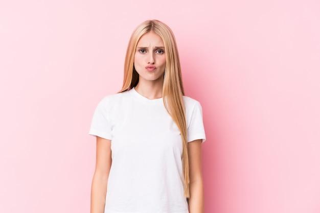 Junge blonde frau auf rosafarbener wand brennt backen durch, hat müden ausdruck. gesichtsausdruck konzept. Premium Fotos