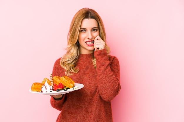 Junge blonde frau, die ein waffeldessert isst, isolierte beißende fingernägel, nervös und sehr ängstlich. Premium Fotos