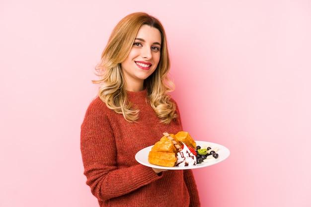 Junge blonde frau, die ein waffeldessert isst, schaut beiseite lächelnd, fröhlich und angenehm Premium Fotos