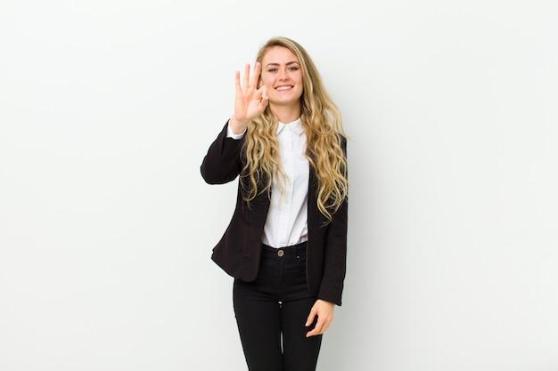 Junge blonde frau, die freundlich lächelt und schaut und nr. drei zeigt Premium Fotos