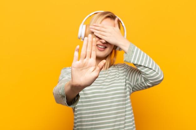 Junge blonde frau, die gesicht mit hand bedeckt und andere hand nach vorne legt, um kamera zu stoppen, fotos oder bilder ablehnend Premium Fotos