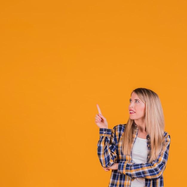 Junge blonde frau, die ihren finger aufwärts schaut oben gegen einen orange hintergrund zeigt Kostenlose Fotos