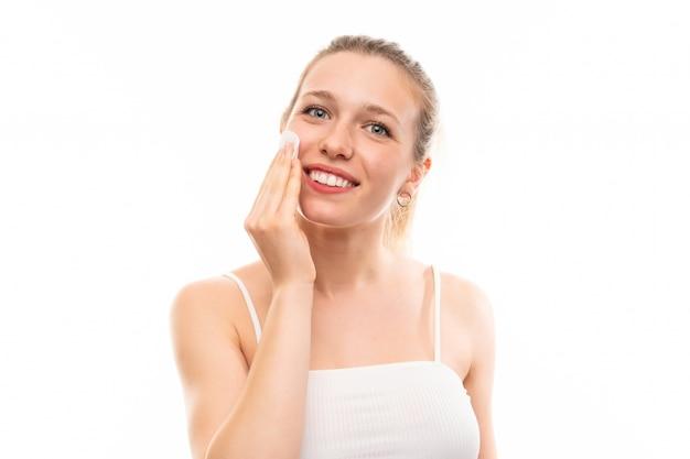 Junge blonde frau, die verfassung von ihrem gesicht mit baumwollauflage entfernt Premium Fotos