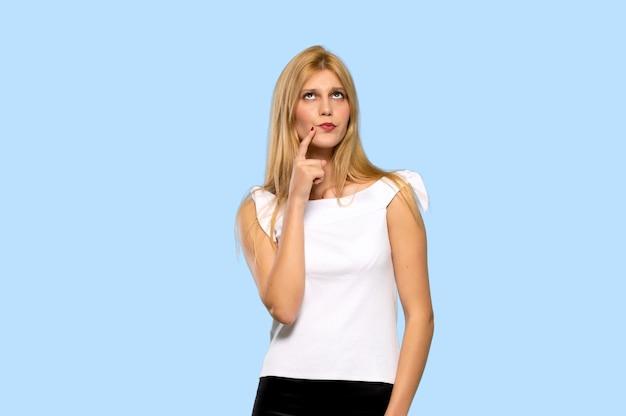 Junge blonde frau, die zur front mit überzeugtem gesicht auf lokalisiertem blauem hintergrund lächelt und schaut Premium Fotos