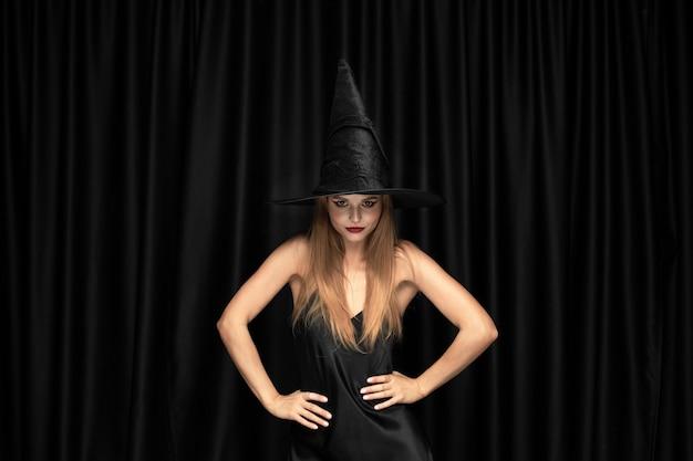 Junge blonde frau im schwarzen hut und im kostüm auf schwarzem hintergrund. attraktives, sinnliches kaukasisches weibliches modell. halloween, schwarzer freitag, cyber montag, verkauf, herbst Kostenlose Fotos