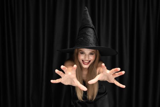 Junge blonde frau im schwarzen hut und im kostüm auf schwarzem hintergrund. attraktives, sinnliches weibliches model. halloween, schwarzer freitag, cyber montag, verkauf, herbst Kostenlose Fotos