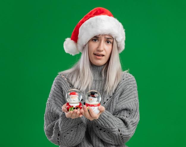 Junge blonde frau im winterpullover und in der weihnachtsmannmütze, die weihnachtsspielzeug-schneekugeln betrachten, die die kamera verwirrt betrachten, die über grünem hintergrund steht Kostenlose Fotos