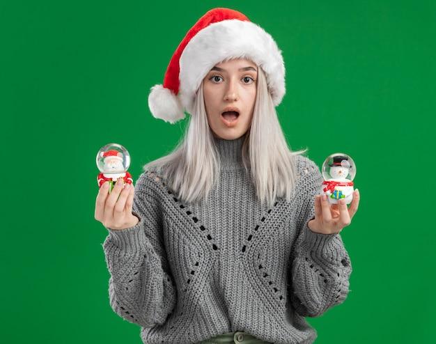 Junge blonde frau im winterpullover und in der weihnachtsmannmütze, die weihnachtsspielzeug-schneekugeln betrachten, die kamera betrachten, die über grünem hintergrund steht Kostenlose Fotos