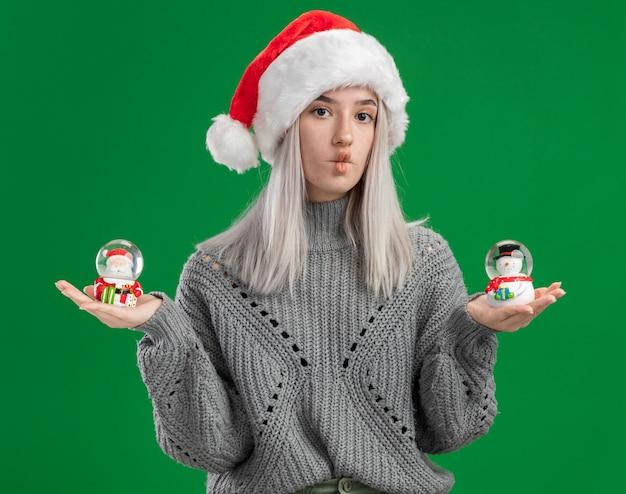 Junge blonde frau im winterpullover und in der weihnachtsmannmütze, die weihnachtsspielzeug-schneekugeln betrachten, die kamera verwirrt betrachten, die zweifel haben, die über grünem hintergrund stehen Kostenlose Fotos