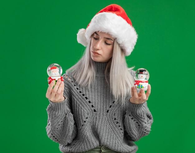 Junge blonde frau im winterpullover und in der weihnachtsmannmütze, die weihnachtsspielzeug-schneekugeln halten, die fasziniert stehen über grünem hintergrund stehen Kostenlose Fotos