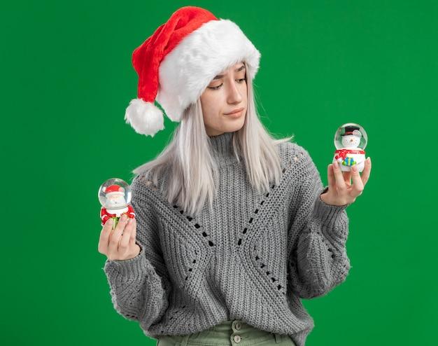 Junge blonde frau im winterpullover und in der weihnachtsmannmütze, die weihnachtsspielzeug-schneekugeln halten, die verwirrt versuchen, wahl zu treffen, die über grünem hintergrund steht Kostenlose Fotos
