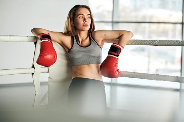 Junge blonde frau in den roten boxhandschuhen und im trainingsanzug, die durch fenster schauen, während durch die stangen der sportbahn nach dem training stehen Premium Fotos