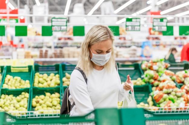 Junge blonde frau in einer medizinischen maske wählt früchte in einem großen hypermarkt. gesundheit und richtige ernährung während einer pandemie. Premium Fotos