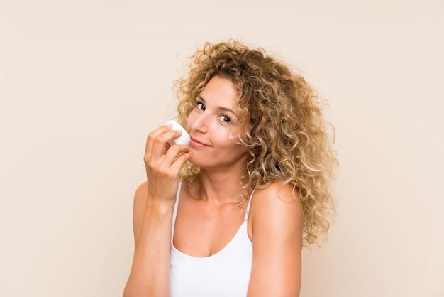 Junge blonde frau mit dem lockigen haar mit feuchtigkeitscreme Premium Fotos