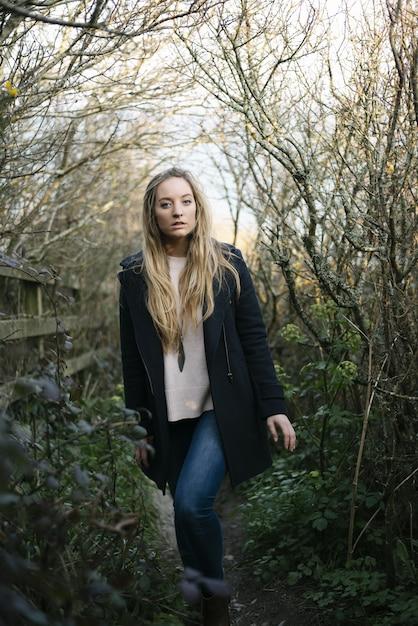 Junge blonde frau mit einem schwarzen mantel, der auf einem weg steht, der von blattlosen bäumen umgeben ist Kostenlose Fotos