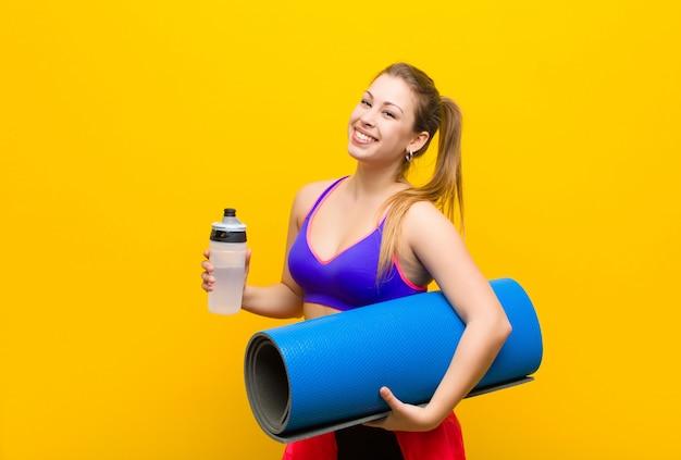 Junge blonde frau mit einem yogamatten-sportkonzept Premium Fotos
