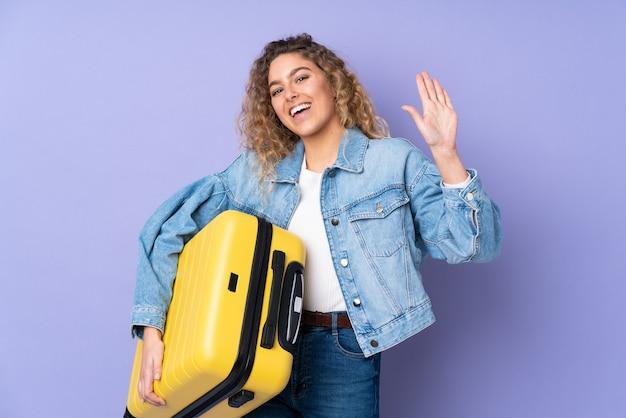 Junge blonde frau mit lockigem haar lokalisiert auf purpur im urlaub mit reisekoffer und gruß Premium Fotos
