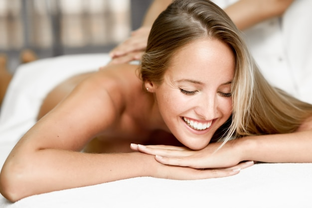 Junge blonde frau mit massage und lächelnd im spa Kostenlose Fotos