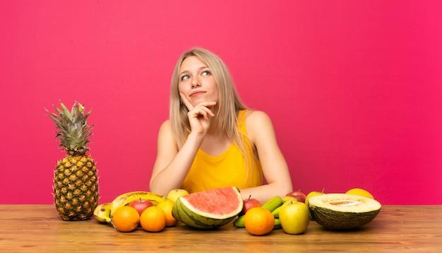 Junge blonde frau mit vielen früchten eine idee denkend Premium Fotos