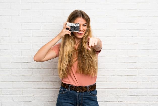 Junge blonde frau über der weißen backsteinmauer, die eine kamera anhält Premium Fotos