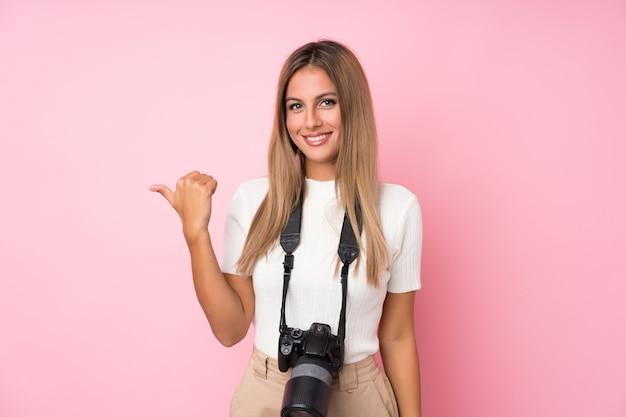 Junge blonde frau über getrennter rosafarbener wand mit einer berufskamera und zeigen auf die seite Premium Fotos