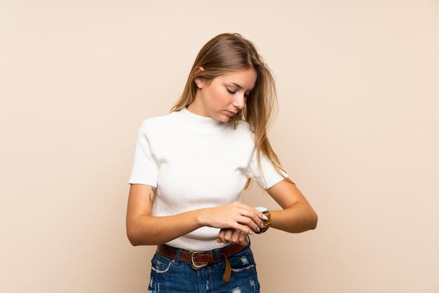 Junge blonde frau über getrennter wand mit armbanduhr Premium Fotos