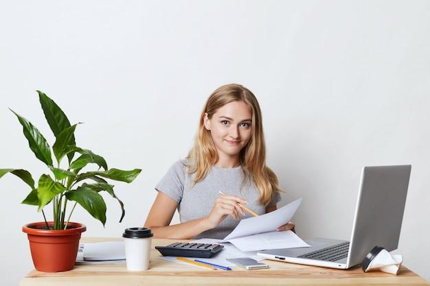 Junge blonde geschäftsfrau, die an ihrem arbeitsplatz sitzt, während geschäftsbericht erstellt, jahreszahlen berechnet, dokumente liest und moderne technologien für ihre arbeit verwendet, kaffee zum mitnehmen trinkt Kostenlose Fotos