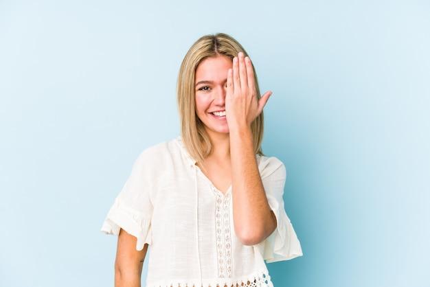 Junge blonde kaukasische frau isoliert, die spaß hat, die hälfte des gesichts mit handfläche bedeckt. Premium Fotos