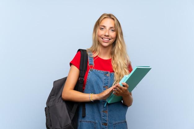 Junge blonde kursteilnehmerfrau über getrenntem blauem wandapplaudieren Premium Fotos