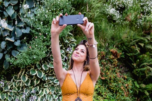 Junge blonde schönheit an der straße, die ein foto mit handy und dem lächeln macht. sommerzeit, grüner hintergrund Premium Fotos