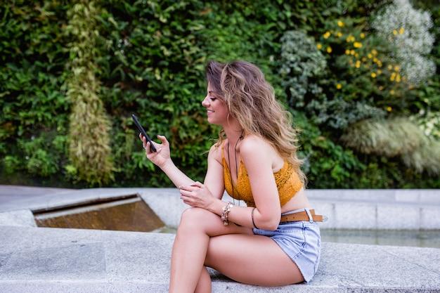 Junge blonde schönheit an der straße unter verwendung des handys und des lächelns. sommerzeit, grüner hintergrund Premium Fotos